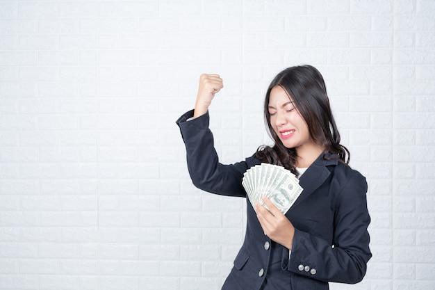 Business woman holding banconote, in contanti separatamente, muro di mattoni bianchi fatto gesti con il linguaggio dei segni.