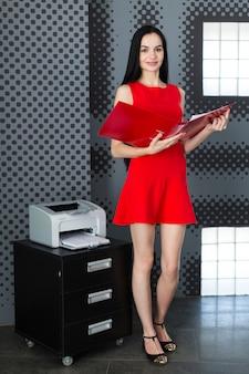 Businesslady attraente in abito rosso e occhiali sta vicino alla stampante e tiene la cartella di carta