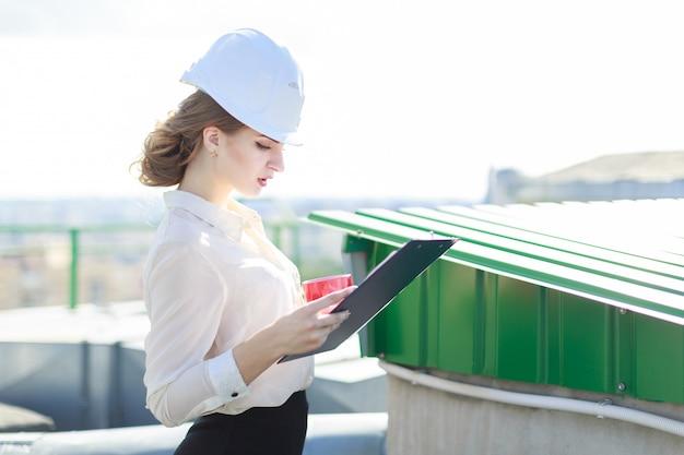 Businesslady attraente in camicetta bianca, orologio, casco e gonna nera stanno sul tetto e tengono tablet e tazza di caffè