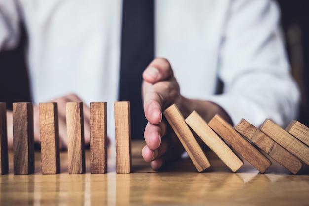 Businessman hand stopping falling dominoes effetto legno da continuo rovesciato o rischio