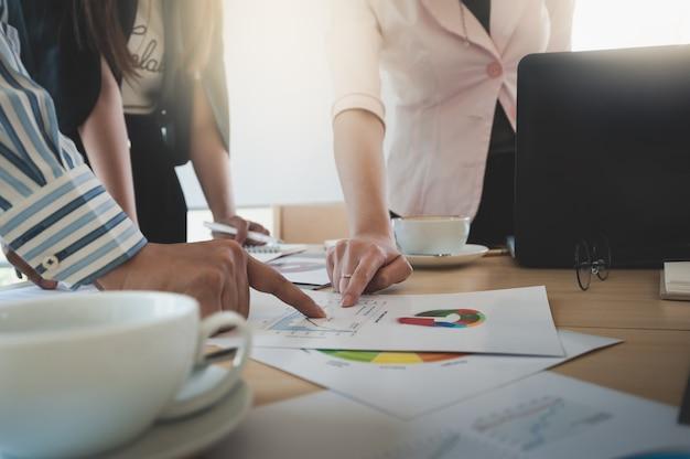 Businesspeople poiting al documento sul tavolo