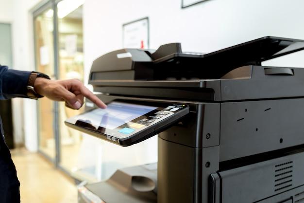 Bussiness man mano premere il pulsante sul pannello della stampante, stampante laser scanner ufficio macchina copia inizio concetto.