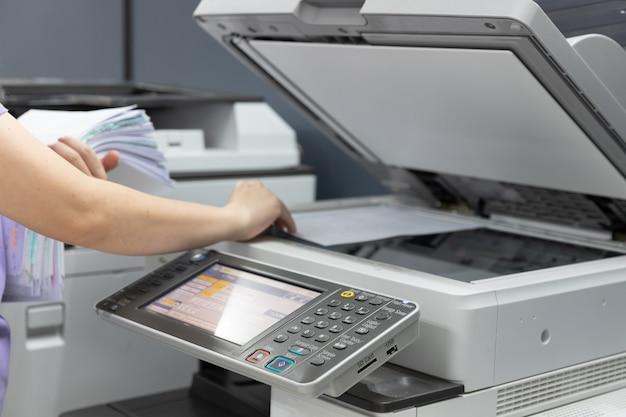 Bussinesswoman che utilizza la macchina della fotocopiatrice per copiare documenti.