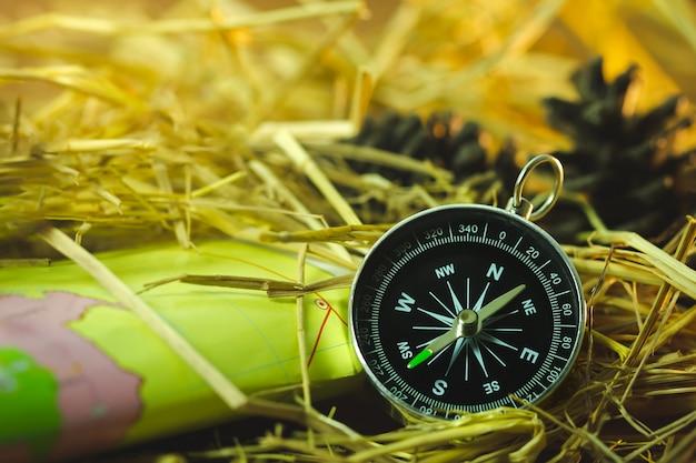 Bussola con mappe di carta e fiori di pino posizionati sulla paglia di grano secco alla luce solare del mattino.