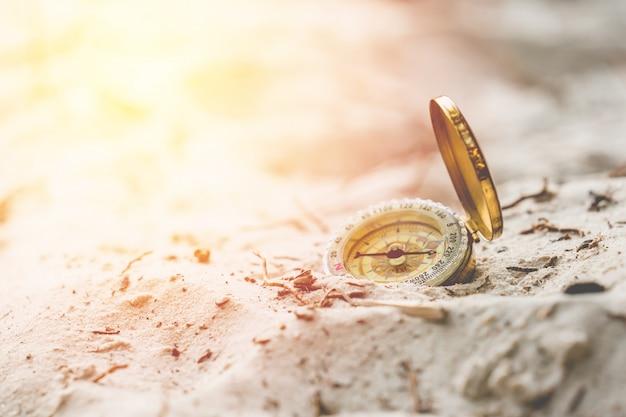 Bussola dell'annata sulla fine della spiaggia della sabbia su