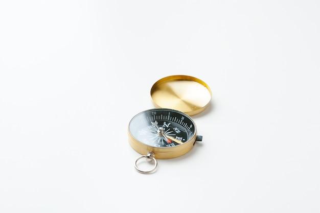 Bussola dorata dell'annata isolata su bianco