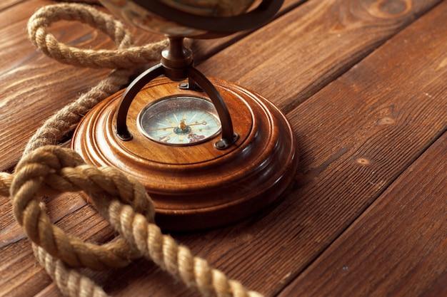 Bussola e corda sul tavolo di legno. avvicinamento
