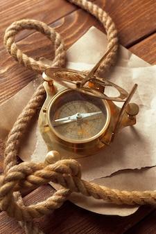 Bussola e corda sulla tavola di legno