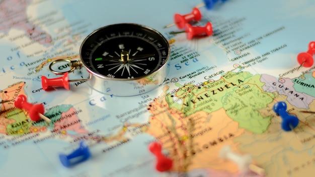 Bussola magnetica e puntine sulla mappa.
