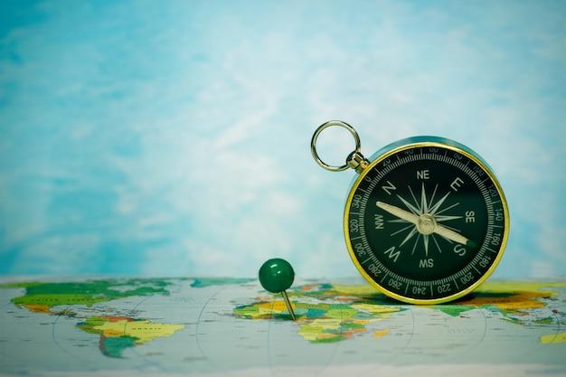 Bussola magnetica sulla mappa del mondo, concetto di viaggio e destinazione, macro viaggio