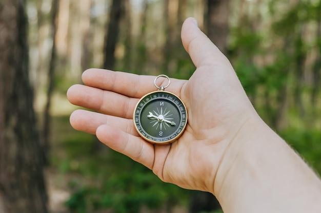 Bussola nella mano di un ragazzo sulla foresta. concetto sul tema del turismo.