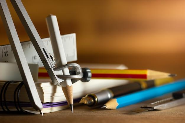 Bussola per disegno e stazionaria sul tavolo di legno. concetto di studio di architettura o ritorno a scuola. primo piano e copia spazio per il testo.