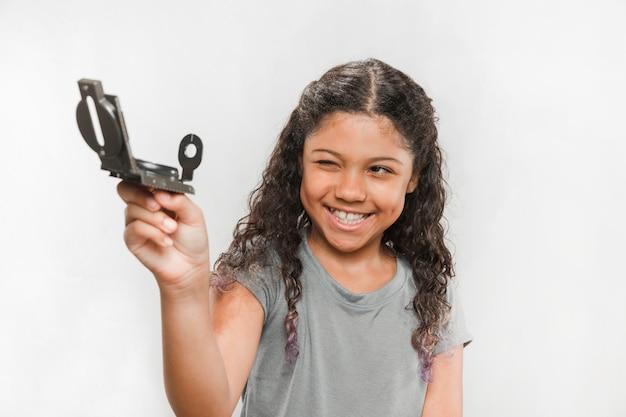 Bussola sorridente della holding della ragazza contro priorità bassa bianca