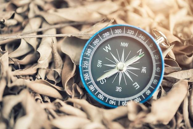 Bussola su foglie secche con luce. strumento per determinare le direzioni poste.