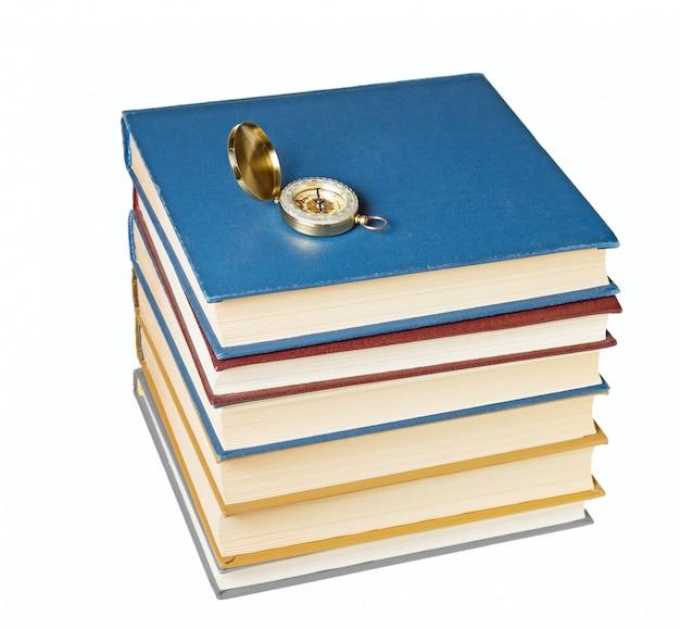 Bussola su una pila di libri isolato su sfondo bianco