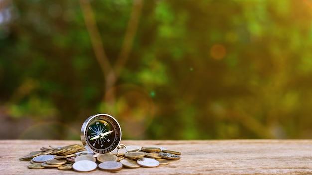Bussola sul mucchio di monete d'oro al vecchio tavolo di legno
