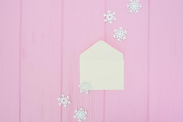 Busta bianca aperta con i fiocchi di neve di natale su di legno rosa