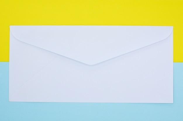 Busta bianca posta su sfondo blu e giallo