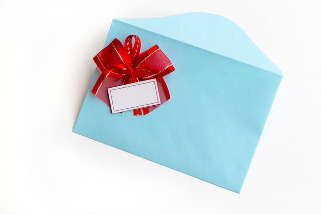 Busta blu di carta in bianco con l'arco rosso del nastro sulla vista bianca e piana, vista superiore.
