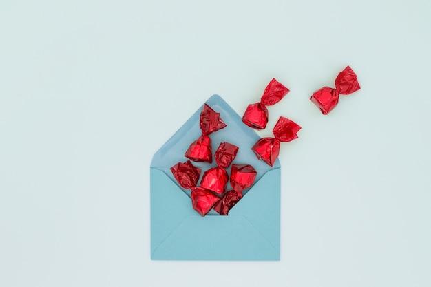 Busta con caramelle rosse su superficie blu