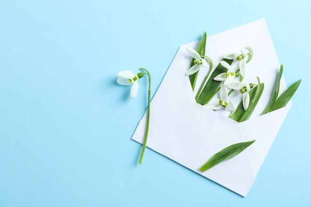 Busta con fiori bucaneve su sfondo di colore, spazio per il testo
