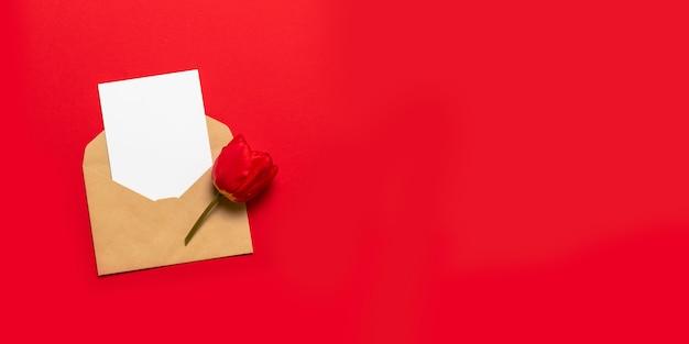 Busta con spazio per testo e tulipano rosso su sfondo rosso