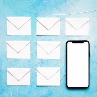 Busta del libro bianco delle icone del messaggio con il cellulare su fondo blu