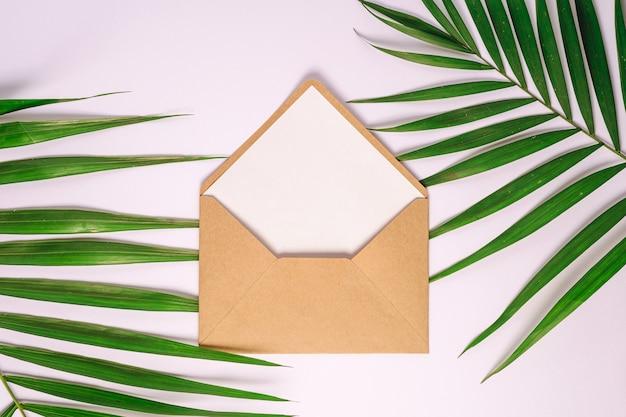 Busta della carta marrone di kraft con la carta vuota bianca sulle foglie di palma, fondo bianco, lettera in bianco del modello
