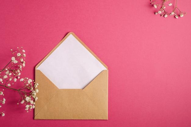 Busta di carta marrone kraft con carta bianca vuota, fiori di gypsophila, sfondo rosa rosso, modello di mockup