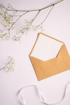 Busta di carta marrone kraft con carta vuota bianca, fiori di gypsophila e nastro in tessuto, sfondo bianco, lettera vuota mockup
