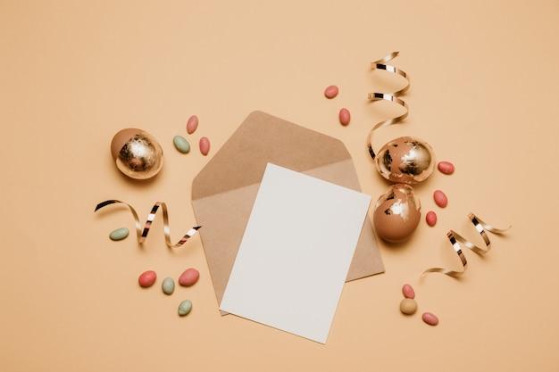 Busta in bianco del mestiere con un foglio di carta colto su una priorità bassa beige. uova di pasqua dorate con la caramella dei fagioli di gelatina, vista superiore.