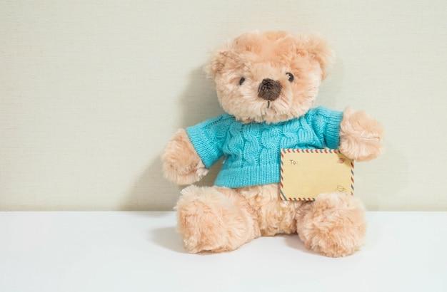 Busta marrone con bambola di orso bruno sulla parete
