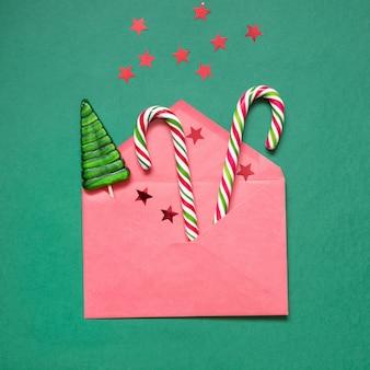 Busta natalizia con bastoncino di zucchero, glitter stelle su verde. biglietto di auguri di natale. vista dall'alto.