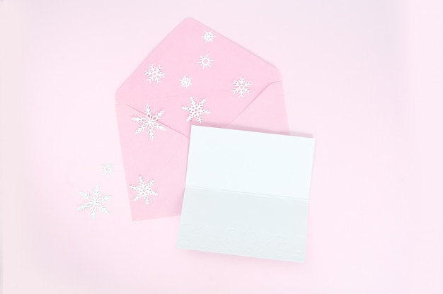 Busta rosa aperta con fiocchi di neve di natale e foglio di carta bianca
