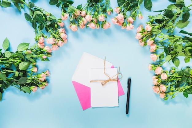 Busta rosa; carta; la penna e le rose fioriscono la decorazione su fondo blu