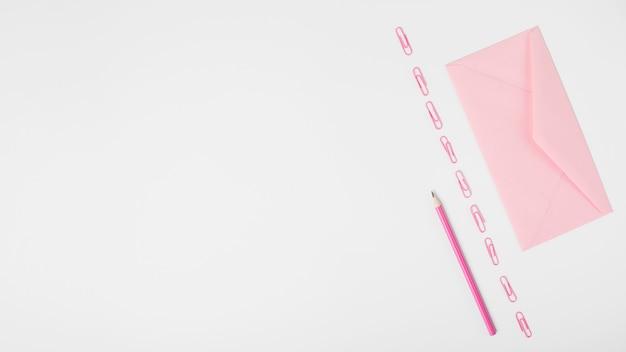 Busta rosa e fila di graffette e matita su sfondo bianco