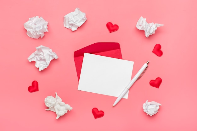 Busta rossa, carta da lettere bianca, cupido, cuori, penna, carta stropicciata su sfondo rosa buon san valentino concetto