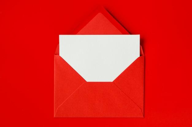 Busta rossa con carta bianca vuota. san valentino sullo sfondo. mockup di lettera d'amore.