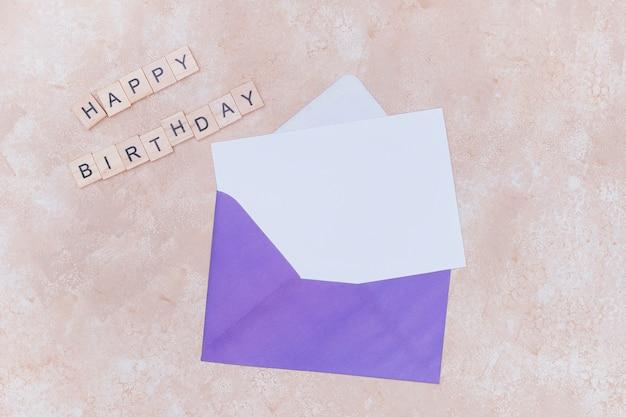 Busta viola con invito di compleanno bianco mock up