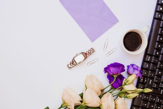 Busta viola; orologio da polso; graffetta per fogli; tazza di caffè; tastiera e fiori di eustoma su sfondo bianco