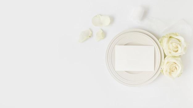 Busta vuota sul piatto con rose e nastro arrotolato su sfondo bianco