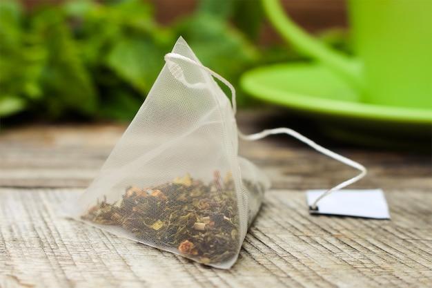 Bustina di tè su sfondo di menta e tazza verde
