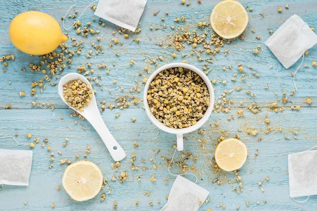 Bustina di the; secchi fiori di crisantemo cinese in tazza; e fette di limone sul tavolo