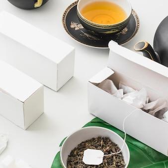 Bustine di tè nella scatola bianca con tisana su sfondo bianco