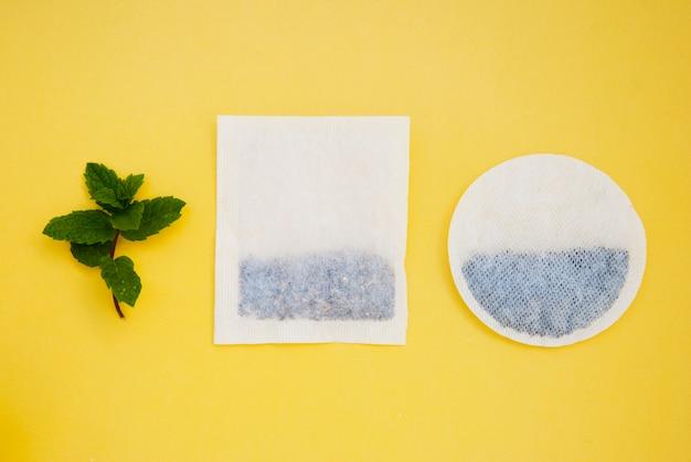 Bustine di tè rotonde e quadrate su giallo e foglie di menta, con copyspace. bevande e bevande