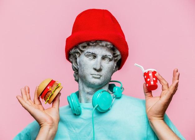 Busto antico del maschio in cappello con bevanda cola e hamburger