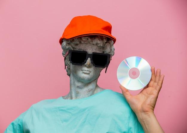 Busto antico di maschio in cappuccio con occhiali da sole e cd