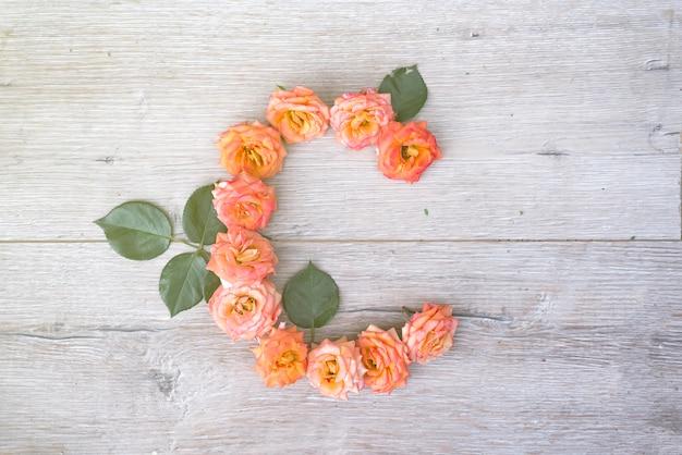C, alfabeto del fiore delle rose isolato su fondo di legno grigio, disposizione piana