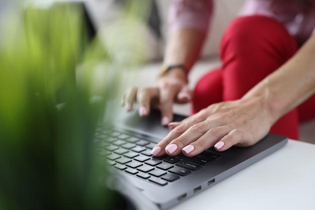 C'è un laptop sul tavolo. le mani femminili stanno digitando il testo.
