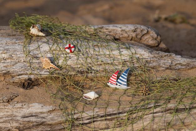 C'è un vecchio tronco sulla sabbia, una rete da pesca, una nave, un'ancora, un volante e conchiglie